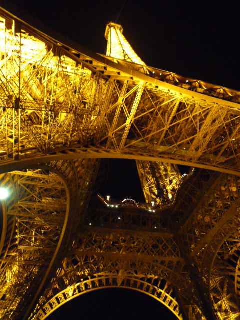 The Eiffel tower illuminated and seen from below